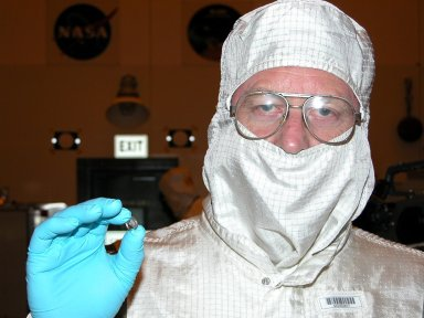 KENNEDY SPACE CENTER, FLA. - Jim Lloyd, with the Mars Exploration Rover program, holds a computer chip with about 35,000 laser-engraved signatures of visitors to the Jet Propulsion Laboratory. The chip will be placed on the second rover to be launched to Mars (MER-1/MER-B); the first rover already has one. The signatures include those of senators, artists, and John Glenn. The identical Mars rovers are scheduled to launch June 5 and June 25 from Cape Canaveral Air Force Station.