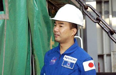 KENNEDY SPACE CENTER, FLA. - Astronaut Soichi Noguchi, with the National Space Development Agency of Japan (NASDA), looks at the Japanese Experiment Module after its arrival at Port Canaveral, Fla. Built by the Tsukuba Space Center near Tokyo, the pressurized module is the first element of the JEM, Japan?s primary contribution to the space station, to be delivered to KSC. It will enhance the unique research capabilities of the orbiting complex by providing an additional shirt-sleeve environment for astronauts to conduct science experiments. The JEM also includes two logistics modules, an exposed pallet for space environment experiments and a robotic manipulator system that are still under construction in Japan. The various JEM components will be assembled in space over the course of three space shuttle missions. .