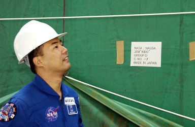 KENNEDY SPACE CENTER, FLA. - Astronaut Soichi Noguchi, with the National Space Development Agency of Japan (NASDA), looks at the Japanese Experiment Module after its arrival at Port Canaveral, Fla. Built by the Tsukuba Space Center near Tokyo, the pressurized module is the first element of the JEM, Japan?s primary contribution to the space station, to be delivered to KSC. It will enhance the unique research capabilities of the orbiting complex by providing an additional shirt-sleeve environment for astronauts to conduct science experiments. The JEM also includes two logistics modules, an exposed pallet for space environment experiments and a robotic manipulator system that are still under construction in Japan. The various JEM components will be assembled in space over the course of three space shuttle missions.