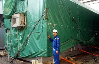 KENNEDY SPACE CENTER, FLA. - Astronaut Soichi Noguchi, with the National Space Development Agency of Japan (NASDA), stands next to the Japanese Experiment Module after its arrival at Port Canaveral, Fla. Built by the Tsukuba Space Center near Tokyo, the pressurized module is the first element of the JEM, Japan?s primary contribution to the space station, to be delivered to KSC. It will enhance the unique research capabilities of the orbiting complex by providing an additional shirt-sleeve environment for astronauts to conduct science experiments. The JEM also includes two logistics modules, an exposed pallet for space environment experiments and a robotic manipulator system that are still under construction in Japan. The various JEM components will be assembled in space over the course of three space shuttle missions.