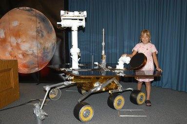 "KENNEDY SPACE CENTER, FLA. - Sofi Collis, the third grade student winner of the ""Name the Rovers"" contest, poses with a model of a rover. The names she proposed -- Spirit and Opportunity -- were announced today in a press conference held by NASA Administrator Sean O'Keefe. NASA's twin Mars Exploration Rovers are designed to study the history of water on Mars. These robotic geologists are equipped with a robotic arm, a drilling tool, three spectrometers, and four pairs of cameras that allow them to have a human-like, 3D view of the terrain. Each rover could travel as far as 100 meters in one day to act as Mars scientists' eyes and hands, exploring an environment where humans are not yet able to go. MER-A, with the rover Spirit aboard, is scheduled to launch on June 8 at 2:06 p.m. EDT, with two launch opportunities each day during a launch period that closes on June 24."