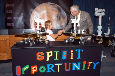 "KENNEDY SPACE CENTER, FLA. - Nine-year-old Sofi Collis (left) is congratulated by NASA Administrator Sean O'Keefe for selecting the names of the Mars Exploration Rovers -- ""Spirit"" and ""Opportunity"" -- during a press conference. The names Sofi suggested were chosen from more than 10,000 student entries in an essay contest managed for NASA by the LEGO Company. NASA's twin Mars Exploration Rovers are designed to study the history of water on Mars. These robotic geologists are equipped with a robotic arm, a drilling tool, three spectrometers, and four pairs of cameras that allow them to have a human-like, 3D view of the terrain. Each rover could travel as far as 100 meters in one day to act as Mars scientists' eyes and hands, exploring an environment where humans are not yet able to go. MER-A, with the rover Spirit aboard, is scheduled to launch on June 8 at 2:06 p.m. EDT, with two launch opportunities each day during a launch period that closes on June 24."