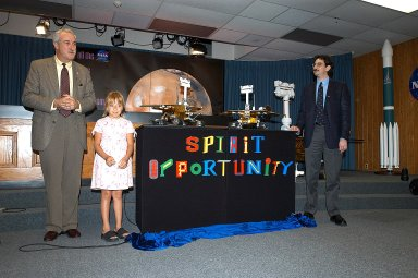 "KENNEDY SPACE CENTER, FLA. - Nine-year-old Sofi Collis proudly presents the names she selected for the Mars Exploration Rovers -- ""Spirit"" and ""Opportunity"" -- during a press conference. Also participating in the press conference are NASA Administrator Sean O'Keefe (left) and Brad Justus, LEGO Co. senior vice president (right). The names Sofi suggested were selected from more than 10,000 student entries in an essay contest managed for NASA by the LEGO Company. NASA's twin Mars Exploration Rovers are designed to study the history of water on Mars. These robotic geologists are equipped with a robotic arm, a drilling tool, three spectrometers, and four pairs of cameras that allow them to have a human-like, 3D view of the terrain. Each rover could travel as far as 100 meters in one day to act as Mars scientists' eyes and hands, exploring an environment where humans are not yet able to go. MER-A, with the rover Spirit aboard, is scheduled to launch on June 8 at 2:06 p.m. EDT, with two launch opportunities each day during a launch period that closes on June 24."