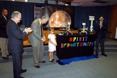 "KENNEDY SPACE CENTER, FLA. - Nine-year-old Sofi Collis unveils the names of the Mars Exploration Rovers -- ""Spirit"" and ""Opportunity"" -- during a press conference. Participating in the press conference are, from left, Dr. John Marburger, science advisor to the President and director of the Office of Science and Technology Policy; NASA Administrator Sean O'Keefe; Sofi Collis, a third grade student from Arizona; and Brad Justus, LEGO Co. senior vice president. The names Sofi suggested were selected from more than 10,000 student entries in an essay contest managed for NASA by the LEGO Company. NASA's twin Mars Exploration Rovers are designed to study the history of water on Mars. These robotic geologists are equipped with a robotic arm, a drilling tool, three spectrometers, and four pairs of cameras that allow them to have a human-like, 3D view of the terrain. Each rover could travel as far as 100 meters in one day to act as Mars scientists' eyes and hands, exploring an environment where humans are not yet able to go. MER-A, with the rover Spirit aboard, is scheduled to launch on June 8 at 2:06 p.m. EDT, with two launch opportunities each day during a launch period that closes on June 24."