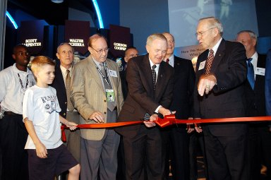 """KENNEDY SPACE CENTER, FLA. - Center Director and former astronaut Roy D. Bridges, Jr., (holding scissors) cuts the ribbon at a ceremony officially opening the U.S. Astronaut Hall of Fame as part of the Kennedy Space Center Visitor Complex. Invited guests and dignitaries look on, such as former astronauts Edgar D. Mitchell on Bridges' left and James Lovell on his right. The ceremony was held in conjunction with the induction of four Space Shuttle astronauts into the Hall of Fame including Daniel Brandenstein, Robert """"Hoot"""" Gibson, Story Musgrave, and Sally Ride. Conceived by six of the Mercury Program astronauts, the U.S. Astronaut Hall of Fame opened in 1990 to provide a place where space travelers could be remembered for their participation and accomplishments in the U.S. space program. The four new inductees join 48 previously honored astronauts from the ranks of the Gemini, Apollo, Skylab, Apollo-Soyuz, and Space Shuttle programs."""