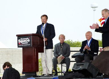 """KENNEDY SPACE CENTER, FLA. - At the KSC Visitor Complex, former astronaut Robert """"Hoot"""" Gibson (at podium) addresses the audience at his induction ceremony into the U.S. Astronaut Hall of Fame. Also standing is former astronaut James A. Lovell. Seated on the dais, from left, are actor and Master of Ceremonies Lance Henriksen and former astronaut John H. Glenn. Also being inducted with Gibson are Space Shuttle astronauts Daniel Brandenstein, Story Musgrave, and Sally K. Ride. Conceived by six of the Mercury Program astronauts, the U.S. Astronaut Hall of Fame opened in 1990 to provide a place where space travelers could be remembered for their participation and accomplishments in the U.S. space program. The four new inductees join 48 previously honored astronauts from the ranks of the Gemini, Apollo, Skylab, Apollo-Soyuz, and Space Shuttle programs."""