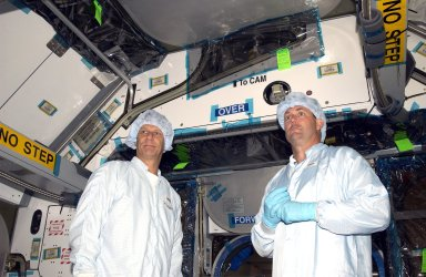 KENNEDY SPACE CENTER, FLA. - STS-120 Mission Specialists Piers Sellers and Michael Foreman check out the inside of the Japanese Experiment Module (JEM) Pressurized Module located in the Space Station Processing Facility. Known as Kibo, the JEM consists of six components: two research facilities -- the Pressurized Module and Exposed Facility; a Logistics Module attached to each of them; a Remote Manipulator System; and an Inter-Orbit Communication System unit. Kibo also has a scientific airlock through which experiments are transferred and exposed to the external environment of space. The various components of JEM will be assembled in space over the course of three Space Shuttle missions. The STS-120 mission will deliver the second of three Station connecting modules, Node 2, which attaches to the end of U.S. Lab. It will provide attach locations for the JEM, European laboratory, the Centrifuge Accommodation Module and later Multi-Purpose Logistics Modules. The addition of Node 2 will complete the U.S. core of the International Space Station.