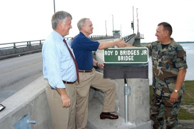 KENNEDY SPACE CENTER, FLA. - From left, incoming KSC Director James W. Kennedy looks on as departing KSC Director Roy D. Bridges Jr. shakes hands with the 45th Space Wing Commander Brig. Gen. J. Gregory Pavlovich. The occasion is the unveiling of the new sign on the NASA Causeway naming the bridge for Bridges who is leaving KSC to become the director of NASA's Langley Research Center, Hampton, Va. The bridge spans the Banana River on the NASA Causeway and connects Kennedy Space Center and Cape Canaveral Air Force Station.
