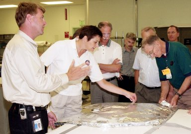 KENNEDY SPACE CENTER, FLA. - Martin Wilson, with United Space Alliance, describes an orbiter?s Thermal Protection System for members of the Stafford-Covey Return to Flight Task Group (SCTG). Handling some of the blanket insulation are Dr. Kathryn Clark and Joe Engle. Third from left is Richard Covey, former Space Shuttle commander, who is co-chair of the SCTG, along with Thomas P. Stafford, Apollo commander. Chartered by NASA Administrator Sean O?Keefe, the task group will perform an independent assessment of NASA?s implementation of the final recommendations by the Columbia Accident Investigation Board.