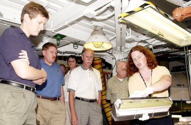 KENNEDY SPACE CENTER, FLA. - NASA worker Joy Huff (right) shows a leading edge subsystems (LESS) with tile bonded to it to members of the Stafford-Covey Return to Flight Task Group (SCTG). From left are Dr. Amy Donahue, David Lengyel, Dr. Kathryn Clark, Richard Covey, former Space Shuttle commander, and William Wegner. Covey is co-chair of the SCTG along with Thomas P. Stafford, Apollo commander. Chartered by NASA Administrator Sean O?Keefe, the task group will perform an independent assessment of NASA?s implementation of the final recommendations by the Columbia Accident Investigation Board.