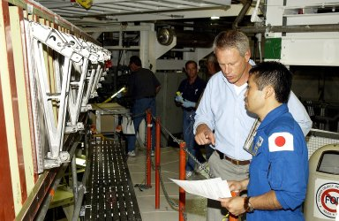KENNEDY SPACE CENTER, FLA. - Japanese astronaut Koichi Wakata (right) listens to William Gaetjens, with the Vehicle Integration Test Team (VITT), who is providing details about the spar installation (left) on the wing of the orbiter Atlantis. Reinforced Carbon Carbon (RCC) panels are mechanically attached to the wing via the spars - a series of floating joints - to reduce loading on the panels caused by wing deflections. The aluminum and the metallic attachments are protected from exceeding temperature limits by internal insulation.