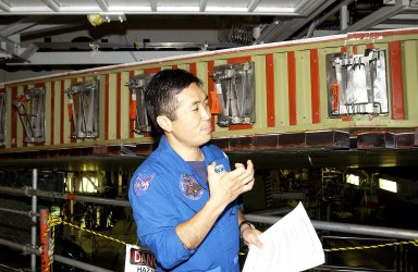KENNEDY SPACE CENTER, FLA. - Japanese astronaut Koichi Wakata gestures as he examines the spar installation (behind him) on the wing of the orbiter Atlantis. Reinforced Carbon Carbon (RCC) panels are mechanically attached to the wing via the spars - a series of floating joints - to reduce loading on the panels caused by wing deflections. The aluminum and the metallic attachments are protected from exceeding temperature limits by internal insulation.