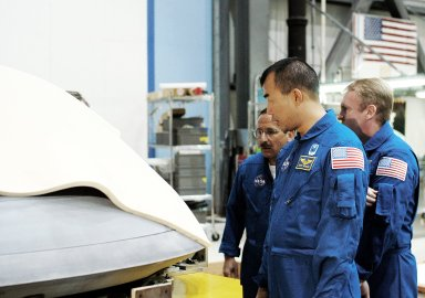 KENNEDY SPACE CENTER, FLA. - In the Orbiter Processing Facility, STS-114 crew members look at the nose cap recently removed from Atlantis. From left are Mission Specialists Charles Camarda, Soichi Noguchi, and Andy Thomas. Camarda and Thomas are new additions to the crew. Noguchi is with the Japan Aerospace Exploration Agency, JAXA. The STS-114 crew is at KSC to take part in crew equipment and orbiter familiarization.