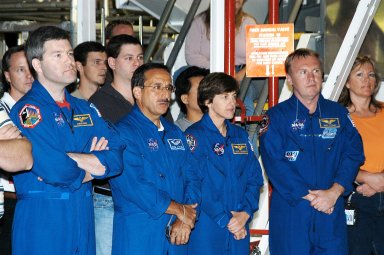 KENNEDY SPACE CENTER, FLA. - While STS-114 Commander Eileen Collins talks to workers in the Orbiter Processing Facility, standing by are (left to right) astronaut Stephen Frick and Mission Specialists Charles Camarda, Wendy Lawrence and Andy Thomas. Frick is a tile specialist who joined the STS-114 crew during crew equipment and orbiter familiarization at KSC.