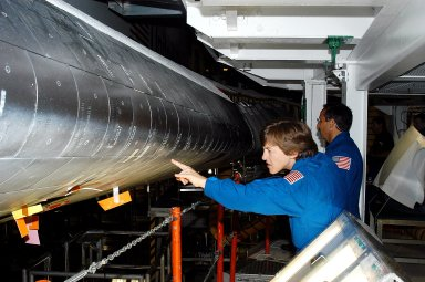 KENNEDY SPACE CENTER, FLA. - In the Orbiter Processing Facility, STS-114 crew members look at the tiles on the wing of Atlantis. In the foreground is Mission Specialist Wendy Lawrence, who is a new addition to the mission crew. Behind her is Mission Specialist Charles Camarda, also a new addition. The STS-114 crew is at KSC to take part in crew equipment and orbiter familiarization.