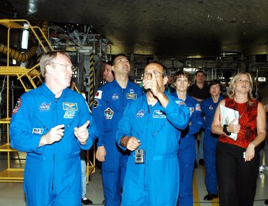 KENNEDY SPACE CENTER, FLA. - The STS-114 mission crew walks through the Orbiter Processing Facility looking at the tiles underneath Atlantis. From left are Mission Specialists Andy Thomas, Stephen Robinson, Soichi Noguchi and Charles Camarda (pointing); Commander Eileen Collins; and Mission Specialist Wendy Lawrence. At far right Glenda Laws, EVA Task Leader, with United Space Alliance at Johnson Space Center. Not seen is Pilot James Kelly. Noguchi is with the Japan Aerospace Exploration Agency, JAXA. The STS-114 crew is at KSC to take part in crew equipment and orbiter familiarization.