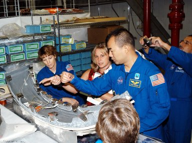 KENNEDY SPACE CENTER, FLA. - Members of the STS-114 crew look over flight equipment in the Orbiter Processing Facility. From left are Mission Commander Eileen Collins; Glenda Laws, EVA Task Leader, with United Space Alliance at Johnson Space Center; and Mission Specialists Soichi Noguchi and Charles Camarda. In the foreground is Mission Specialist Wendy Lawrence. Noguchi is with the Japan Aerospace Exploration Agency, JAXA. Not seen are Pilot James Kelly and Mission Specialists Andy Thomas and Stephen Robinson. The STS-114 crew is at KSC to take part in crew equipment and orbiter familiarization.