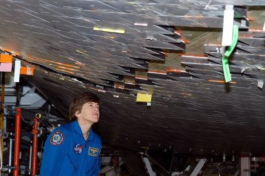KENNEDY SPACE CENTER, FLA. - In the Orbiter Processing Facility, STS-114 Mission Specialist Wendy Lawrence takes a close look at the some of the tiles underneath Atlantis. Lawrence is a new addition to the mission crew. The STS-114 crew is at KSC to take part in crew equipment and orbiter familiarization.