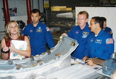 KENNEDY SPACE CENTER, FLA. - Members of the STS-114 crew look over flight equipment in the Orbiter Processing Facility. From left are Glenda Laws, EVA Task Leader, with United Space Alliance at Johnson Space Center, Mission Specialists Soichi Noguchi, Andy Thomas, Charles Camarda and Wendy Lawrence. Noguchi is with the Japan Aerospace Exploration Agency, JAXA. Not seen are Mission Commander Eileen Collins, Pilot James Kelly and Mission Specialist Stephen Robinson. The STS-114 crew is at KSC to take part in crew equipment and orbiter familiarization.
