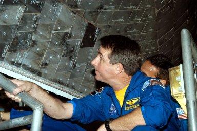 KENNEDY SPACE CENTER, FLA. - In the Orbiter Processing Facility, STS-114 Mission Specialist Stephen Robinson looks closely at the tiles underneath the orbiter Atlantis. The STS-114 crew is at KSC to take part in crew equipment and orbiter familiarization.