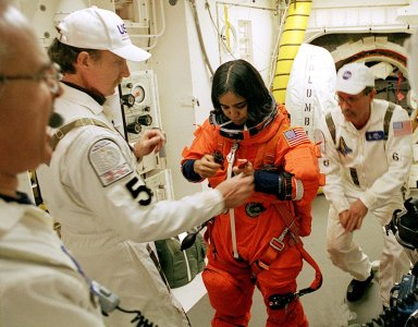 KENNEDY SPACE CENTER, FLA. -- STS-107 Mission Specialist Kalpana Chawla gets help with her launch and entry suit from the Closeout Crew in the White Room. The environmentally controlled chamber is mated to Space Shuttle Columbia for entry into the Shuttle. The hatch is seen in the background right. STS-107 is a mission devoted to research and will include more than 80 experiments that will study Earth and space science, advanced technology development, and astronaut health and safety. The payload on Space Shuttle Columbia includes FREESTAR (Fast Reaction Experiments Enabling Science, Technology, Applications and Research) and the SHI Research Double Module (SHI/RDM), known as SPACEHAB. Experiments on the module range from material sciences to life sciences. Liftoff is scheduled for 10:39 a.m. EST.