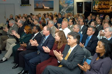 KENNEDY SPACE CENTER, FLA. -- In the KSC television studio, KSC management and other employees applaud President George W. Bush, who addressed the public and an assembly of government officials at NASA Headquarters as he outlined a new focus and vision for the space agency. Seated in the front row, left to right, are Bill Pickavance vice president and associate program manager of Florida Operations, United Space Alliance (USA) ; Howard DeCastro, vice president and Space Shuttle program manager, USA; Shannon Roberts, with External Affairs; Woodrow Whitlow, KSC deputy director; Bruce Buckingham, assistant to Dr. Whitlow; Lisa Malone, director of External Affairs; Ken Aguilar, chief, Equal Opportunity office; and Cheryl Cox, External Affairs. The President stated his goals for NASA?s new mission: Completing the International Space Station, retiring the Space Shuttle orbiters, developing a new crew exploration vehicle, and returning to the moon and beyond within the next two decades. Pres. Bush was welcomed by NASA Administrator Sean O?Keefe and Expedition 8 Commander Michael Foale, who greeted him from the International Space Station. Members of the Washington, D.C., audience included astronauts Eileen Collins, Ed Lu and Michael Lopez-Alegria, and former astronaut Gene Cernan.