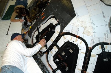 KENNEDY SPACE CENTER, FLA. -- Les Hanks (foreground) and Darlene Beville (background), with United Space Alliance, prepare a window on Atlantis for removal. The windows are being removed to inspect them for contaminants in the thermal seal. Atlantis has been undergoing routine maintenance in the Orbiter Processing Facility for Return to Flight, on mission STS-114.