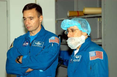 KENNEDY SPACE CENTER, FLA. - In the Space Station Processing Facility, astronaut Lee Archambault and STS-114 Mission Specialist Charles Camarda watch as crew members work with equipment that will be used on the mission. Archambault supports launch and landing operations at the Kennedy Space Center as an Astronaut Office representative. Crew members are at KSC for equipment familiarization. STS-114 is classified as Logistics Flight 1 to the International Space Station, delivering new supplies and replacing one of the orbital outpost?s Control Moment Gyroscopes (CMGs). STS-114 will also carry a Raffaello Multi-Purpose Logistics Module and the External Stowage Platform-2. The crew is slated to conduct at least three spacewalks: They will demonstrate repair techniques of the Shuttle?s Thermal Protection System, replace the failed CMG with one delivered by the Shuttle, and install the External Stowage Platform.