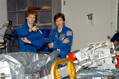 KENNEDY SPACE CENTER, FLA. - STS-114 Commander Eileen Collins and Mission Specialist Wendy Lawrence look over mission equipment in the Space Station Processing Facility. Crew members are at KSC for equipment familiarization. STS-114 is classified as Logistics Flight 1 to the International Space Station, delivering new supplies and replacing one of the orbital outpost?s Control Moment Gyroscopes (CMGs). STS-114 will also carry a Raffaello Multi-Purpose Logistics Module and the External Stowage Platform-2. The crew is slated to conduct at least three spacewalks: They will demonstrate repair techniques of the Shuttle?s Thermal Protection System, replace the failed CMG with one delivered by the Shuttle, and install the External Stowage Platform.