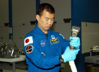 KENNEDY SPACE CENTER, FLA. - STS-114 Mission Specialist Soichi Noguchi, with the Japanese Aerospace Exploration Agency (JAXA), handles equipment that will be used on the mission. He and other crew members are at KSC for equipment familiarization. STS-114 is classified as Logistics Flight 1 to the International Space Station, delivering new supplies and replacing one of the orbital outpost?s Control Moment Gyroscopes (CMGs). STS-114 will also carry a Raffaello Multi-Purpose Logistics Module and the External Stowage Platform-2. The crew is slated to conduct at least three spacewalks: They will demonstrate repair techniques of the Shuttle?s Thermal Protection System, replace the failed CMG with one delivered by the Shuttle, and install the External Stowage Platform.