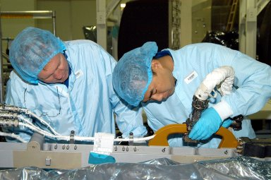KENNEDY SPACE CENTER, FLA. - Dressed in protective suits, STS-114 Mission Specialist Andrew Thomas (left) and Soichi Noguchi, who is with the Japanese Aerospace Exploration Agency (JAXA), handle equipment in the Space Station Processing Facility that will be used on the mission. They and other crew members are at KSC for equipment familiarization. STS-114 is classified as Logistics Flight 1 to the International Space Station, delivering new supplies and replacing one of the orbital outpost?s Control Moment Gyroscopes (CMGs). STS-114 will also carry a Raffaello Multi-Purpose Logistics Module and the External Stowage Platform-2. The crew is slated to conduct at least three spacewalks: They will demonstrate repair techniques of the Shuttle?s Thermal Protection System, replace the failed CMG with one delivered by the Shuttle, and install the External Stowage Platform.
