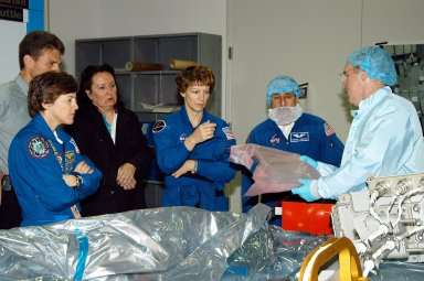 KENNEDY SPACE CENTER, FLA. - STS-114 Mission Specialist Andrew Thomas (right) shows some of the mission equipment to other crew members (from left) Wendy Lawrence, mission specialist; Eileen Collins, commander; and Charles Camarda, mission specialist. Crew members are at KSC for equipment familiarization. STS-114 is classified as Logistics Flight 1 to the International Space Station, delivering new supplies and replacing one of the orbital outpost?s Control Moment Gyroscopes (CMGs). STS-114 will also carry a Raffaello Multi-Purpose Logistics Module and the External Stowage Platform-2. The crew is slated to conduct at least three spacewalks: They will demonstrate repair techniques of the Shuttle?s Thermal Protection System, replace the failed CMG with one delivered by the Shuttle, and install the External Stowage Platform.