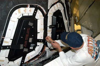 KENNEDY SPACE CENTER, FLA. -- Les Hanks, with United Space Alliance, prepares a window on Atlantis for removal. The windows are being removed to inspect them for contaminants in the thermal seal. Atlantis has been undergoing routine maintenance in the Orbiter Processing Facility for Return to Flight, on mission STS-114.