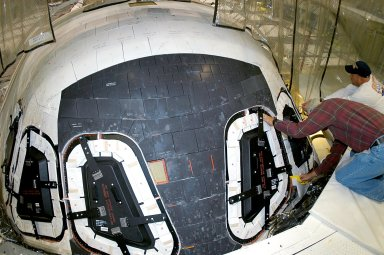 KENNEDY SPACE CENTER, FLA. -- At right, Mike Young and Les Hanks, with United Space Alliance, prepare a window on Atlantis for removal. The windows are being removed to inspect them for contaminants in the thermal seal. Atlantis has been undergoing routine maintenance in the Orbiter Processing Facility for Return to Flight, on mission STS-114.
