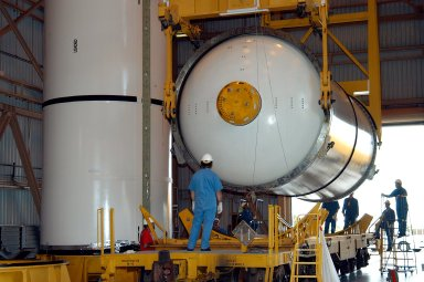 KENNEDY SPACE CENTER, FLA. - In the Rotation Processing and Surge Facility, an SRB solid segment is lowered onto a rail car for shipment to Utah where it will be tested. The segment was part of the STS-114 stack. It is the first time actual flight segments that had been stacked for flight in the VAB are being returned to Utah for testing. It will undergo firing, which will enable inspectors to check the viability of the solid and verify the life expectancy for stacked segments.