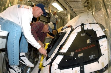 KENNEDY SPACE CENTER, FLA. -- Les Hanks (foreground) and Mike Young (behind him), with United Space Alliance, prepare a window on Atlantis for removal. Behind Young is Lance Emery, with USA, works on tile under the windows. The windows are being removed to inspect them for contaminants in the thermal seal. Atlantis has been undergoing routine maintenance in the Orbiter Processing Facility for Return to Flight, on mission STS-114.
