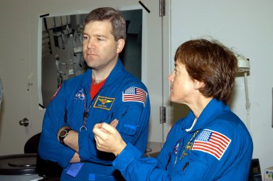 KENNEDY SPACE CENTER, FLA. - In the Space Station Processing Facility, astronaut Stephen Frick and STS-114 Mission Specialist Wendy Lawrence watch as crew members work with equipment that will be used on the mission. Frick is a tile specialist, who joined the STS-114 crew during equipment familiarization at KSC. STS-114 is classified as Logistics Flight 1 to the International Space Station, delivering new supplies and replacing one of the orbital outpost?s Control Moment Gyroscopes (CMGs). STS-114 will also carry a Raffaello Multi-Purpose Logistics Module and the External Stowage Platform-2. The crew is slated to conduct at least three spacewalks: They will demonstrate repair techniques of the Shuttle?s Thermal Protection System, replace the failed CMG with one delivered by the Shuttle, and install the External Stowage Platform.