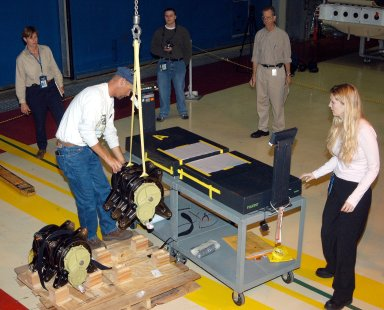 KENNEDY SPACE CENTER, FLA. - Workers in the Orbiter Processing Facility stand by while another guides the lifting of one of two rudder speed brake actuators onto a table to measure the alignment of its bearings. The actuators move an orbiter?s rudder, speed brake, elevons and main engines during flight.