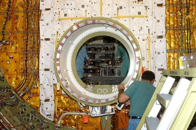 KENNEDY SPACE CENTER, FLA. - A worker in the Orbiter Processing Facility checks the open hatch of the airlock in Discovery?s payload bay. The airlock is normally located inside the middeck of the spacecraft?s pressurized crew cabin. The airlock is sized to accommodate two fully suited flight crew members simultaneously. Support functions include airlock depressurization and repressurization, extravehicular activity equipment recharge, liquid-cooled garment water cooling, EVA equipment checkout, donning and communications. The outer hatch isolates the airlock from the unpressurized payload bay when closed and permits the EVA crew members to exit from the airlock to the payload bay when open.