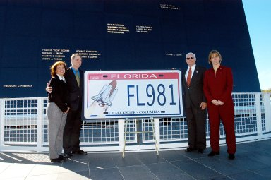 KENNEDY SPACE CENTER, FLA. - The new Florida license plate honoring the fallen astronauts of Challenger and Columbia is unveiled at the KSC Visitor Complex, in front of the Space Memorial Mirror. Participants in the dedication included (from left) Susan Berry, a teacher from Mila Elementary School in Brevard County; Sen. Bill Posey; Florida Rep. Ralph Poppell; and Kirstie McCool Chadwick, sister of William ?Willie? J. McCool, who was the pilot on mission STS-107 that ended in disaster Feb. 1, 2003. The Space Mirror, 42-1/2 feet high by 50 feet wide, illuminates the names of the fallen astronauts cut through the monument?s black granite surface.