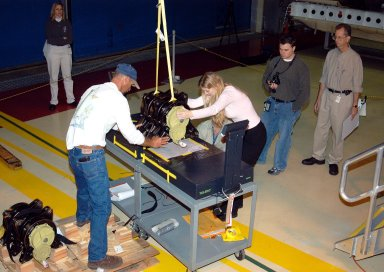 KENNEDY SPACE CENTER, FLA. - Workers in the Orbiter Processing Facility settle into place one of two rudder speed brake actuators onto a table to measure the alignment of its bearings. The actuators move an orbiter?s rudder, speed brake, elevons and main engines during flight.