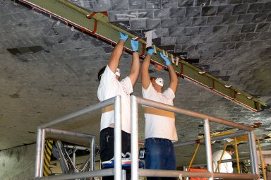 KENNEDY SPACE CENTER, FLA. - In the Orbiter Processing Facility, technicians work on insulation tiles near the landing gear door of orbiter Discovery. The orbiter is now being prepared for eventual launch on a future mission.