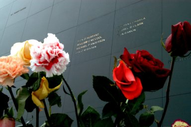 KENNEDY SPACE CENTER, FLA. - Brilliant roses and carnations frame the names of the Columbia crew carved onto the black granite surface of the Astronaut Memorial Mirror at the KSC Visitor Complex. The flowers were left by visitors who attended a memorial service for the crew on the anniversary of the tragic accident that claimed their lives Feb. 1, 2003. The service included comments by Center Director Jim Kennedy, Deputy Director Woodrow Whitlow Jr., Executive Director of Florida Space Authority Winston Scott, and Dr. Stephen Feldman, president of the Astronaut Memorial Foundation, who placed the wreath at the mirror. The mirror honors astronauts who have given their lives for space exploration.
