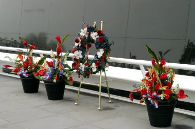 KENNEDY SPACE CENTER, FLA. - A wreath and other floral arrangements rest beneath the Astronaut Memorial Mirror at the KSC Visitor Complex following a memorial service held for the crew of Columbia on the anniversary of the tragic accident that took their lives Feb. 1, 2003. The service included comments by Center Director Jim Kennedy, Deputy Director Woodrow Whitlow Jr., Executive Director of Florida Space Authority Winston Scott, and Dr. Stephen Feldman, president of the Astronaut Memorial Foundation, who placed the wreath at the mirror. The black granite mirror honors astronauts, whose names are carved in the surface, who have given their lives for space exploration.