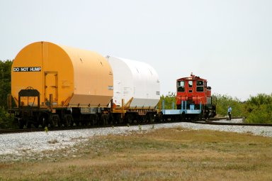KENNEDY SPACE CENTER, FLA. - The red NASA engine hauls its cargo toward Titusville, Fla. The containers enclose segments of a solid rocket booster being returned to Utah for testing. The segments were part of the STS-114 stack. It is the first time actual flight segments that had been stacked for flight in the VAB are being returned for testing. They will undergo firing, which will enable inspectors to check the viability of the solid and verify the life expectancy for stacked segments.