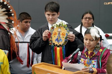 KENNEDY SPACE CENTER, FLA. - A member of the Shoshone-Bannock Native American community from Fort Hall, Idaho, reads a tribute to the crew of Columbia while another displays a handmade item with the STS-107 logo. Dancers from Shoshone-Bannock Junior-Senior High School performed a healing ceremony during the memorial held at the Space Memorial Mirror, in the KSC Visitor Complex. Feb. 1 is the one-year anniversary of the loss of the crew and orbiter Columbia in a tragic accident as the ship returned to Earth following mission STS-107. Students and staff of the Shoshone-Bannock Nation had an experiment on board Columbia. The public was invited to the memorial service, held in the KSC Visitor Complex, which included comments by Center Director Jim Kennedy and Executive Director of Florida Space Authority Winston Scott. Scott is a former astronaut who flew on Columbia in 1997.
