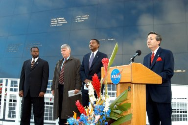 KENNEDY SPACE CENTER, FLA. - At the podium in front of the Space Memorial Mirror at the KSC Visitor Complex is Dr. Stephen Feldman, president of the Astronaut Memorial Foundation. He spoke to attendees at the memorial service remembering and honoring the crew of Columbia. With him (from left) are KSC Deputy Director Woodrow Whitlow Jr., Center Director Jim Kennedy and Executive Director of Florida Space Authority Winston Scott. Feb. 1 is the one-year anniversary of the loss of the crew and orbiter Columbia in a tragic accident as the ship returned to Earth following mission STS-107. Scott is a former astronaut who flew on Columbia in 1997. Attended by many friends, co-workers and families, the memorial service was also open to the public.