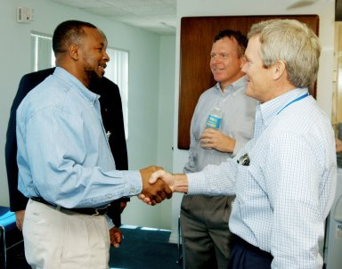 KENNEDY SPACE CENTER, FLA. - At the Beach House, Deputy Director Woodrow Whitlow Jr. (left) greets Bruce Melnick (right), vice president for Boeing Florida Operations at KSC. In the background is Congressman Tom Feeney. During January and February, Congressman Feeney traveled the entire coastline of Florida?s 24th District, and concluded his walks March 1 in Brevard County. On the walks, he met with constituents and community leaders to discuss legislative issues that will be addressed by the 108th Congress.