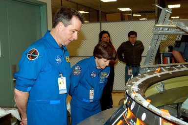 KENNEDY SPACE CENTER, FLA. - Members of the STS-114 crew spend time in the Orbiter Processing Facility becoming familiar with Shuttle and mission equipment. Mission Specialists Stephen Robinson (left) and Wendy Lawrence (right) look at an engine eyelet, which serves as part of the thermal protection system on an orbiter. The STS-114 mission is Logistics Flight 1, which is scheduled to deliver supplies and equipment and the external stowage platform to the International Space Station.