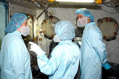 KENNEDY SPACE CENTER, FLA. - In the Space Station Processing Facility, STS-114 Mission Specialist Stephen Robinson (right) learns about the Japanese Experiment Module (JEM) from Louise Kleba (left), with United Space Alliance at KSC, and Jennifer Goldsmith (center), with USA at Johnson Space Center. Crew members are at KSC becoming familiar with Shuttle and mission equipment. The mission is Logistics Flight 1, which is scheduled to deliver supplies and equipment plus the external stowage platform to the International Space Station.